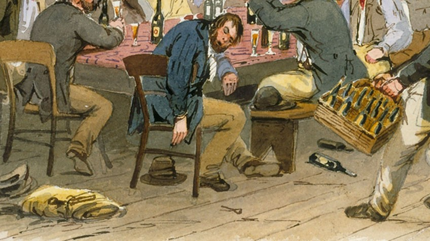 A drunken man is passed out at a table while another man approaches with a carton of beer