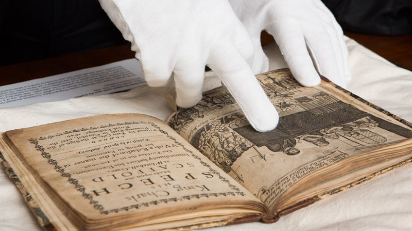 Photo of people looking at a rare book