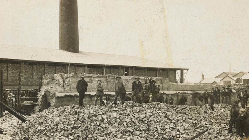 A group of men stand on a pile of brick rubble with a tall chimney in the background
