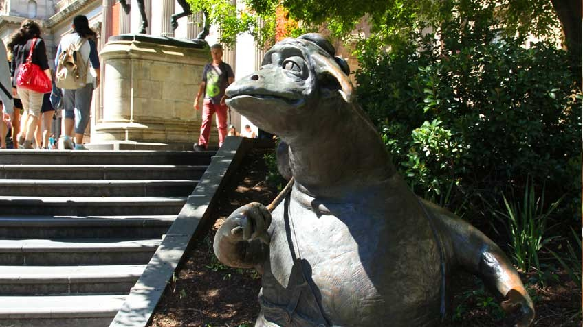 Colour photo of The Bunyip of Berkeley's Creek, Dromkeen sculpture, beside the front steps of State Library Victoria