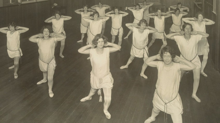 Women in white tunics do stretching exercises in a hall