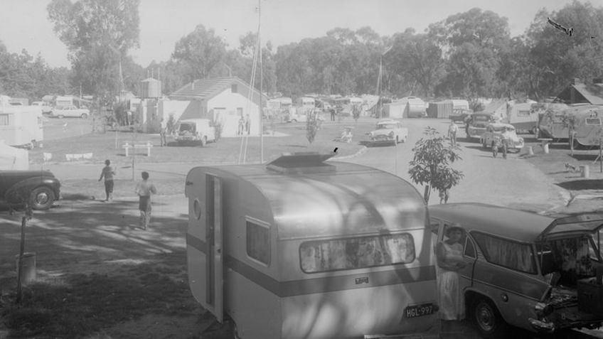 A B&W photo of mid-century cars and caravans parked around an oval