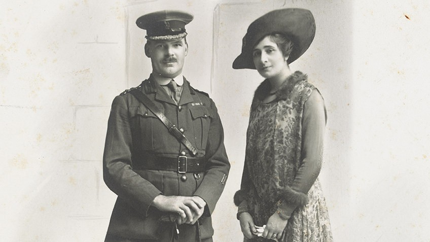 A man in a soldier's uniform and a well-dressed woman wearing a large hat