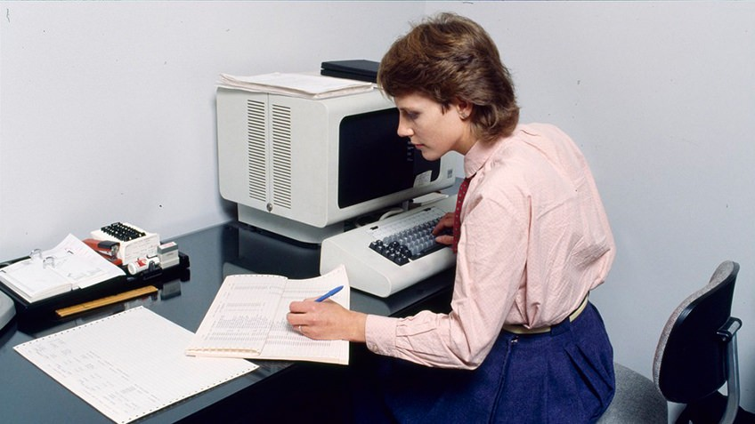 woman wearing pink shirt and blue skirt entering data from spreadsheet into 1980s computer