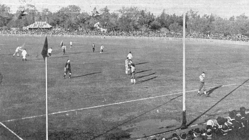 Black and white photo of 1895 football match, with players on the field and spectators in the stand