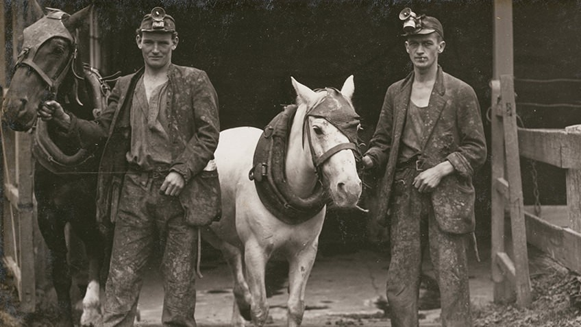 Two young men, whole-length, full face, standing at mine entrance, wearing work soiled clothes and miner's helmets, each man leading a pony
