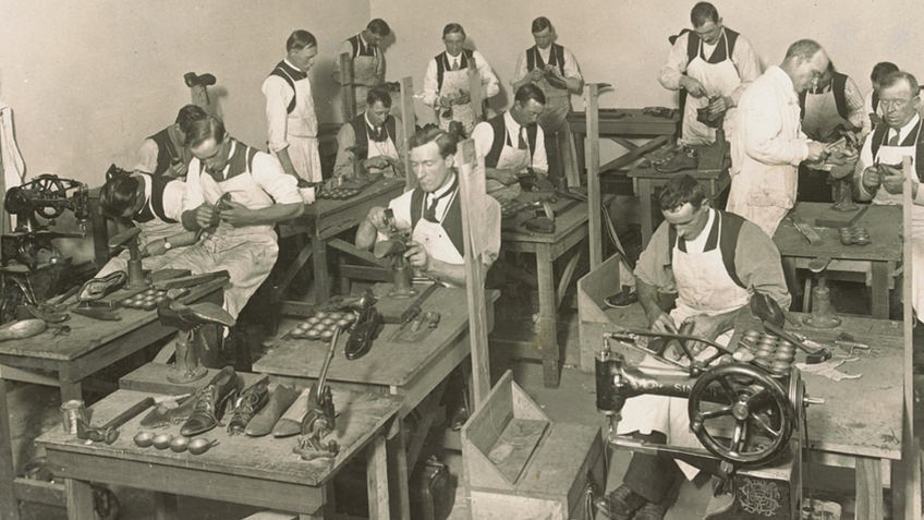 sepia photograph of men at desks and sewing machines repairing shoes and boots