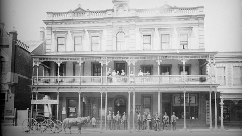 Black and white historic photo of two-storey James' Coffee Palace with men and women standing and sitting under the verandah