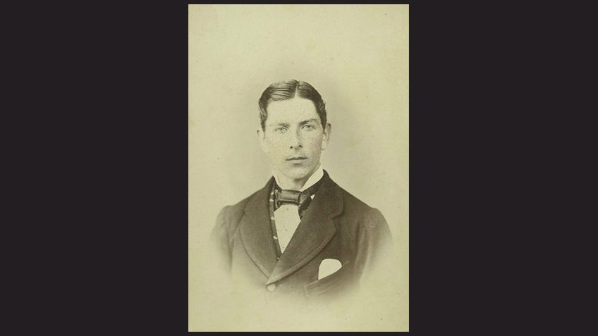 black background with sepia photo of young Victorian-era man wearing cravat
