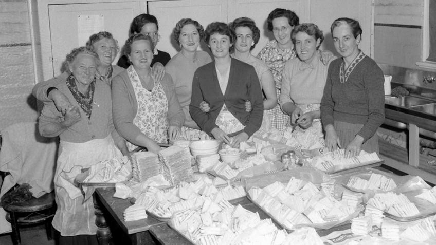 Black and white photo of women crowded around a kitchen table loaded with sandwiches