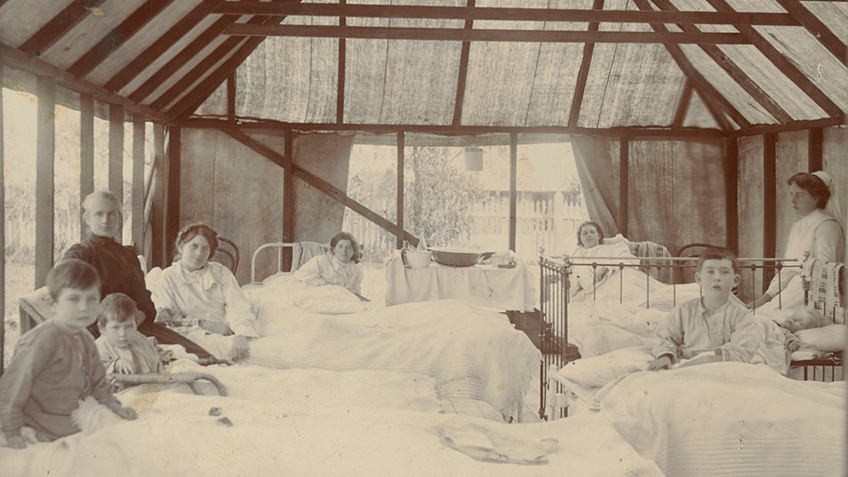 Sepia photo of bed-ridden children in a large tent with a nurse at the side