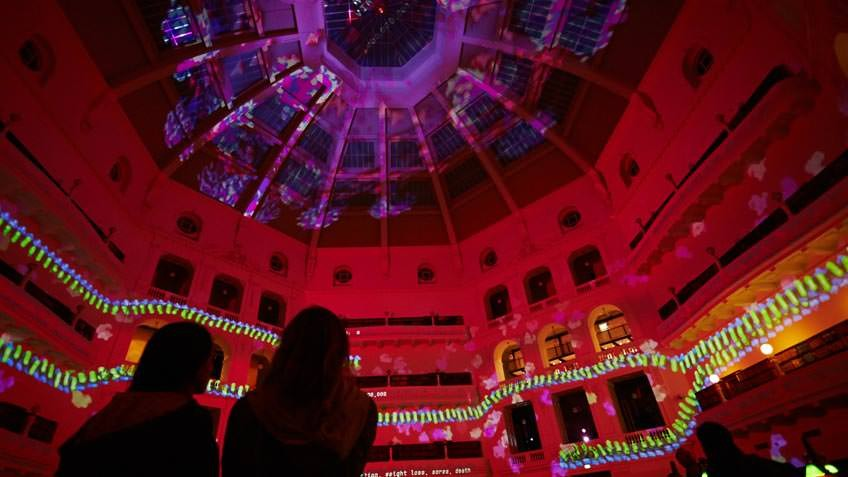 Interior of State Library Victoria's La Trober Reading Room during White Night with red projection covering the dome