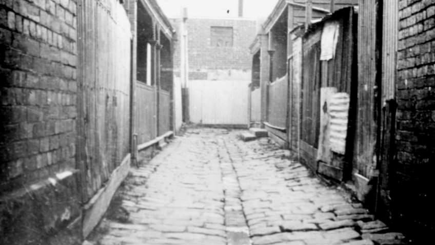 Black and white photo of cobblestone slum alley in Richmond, lined with timer shacks