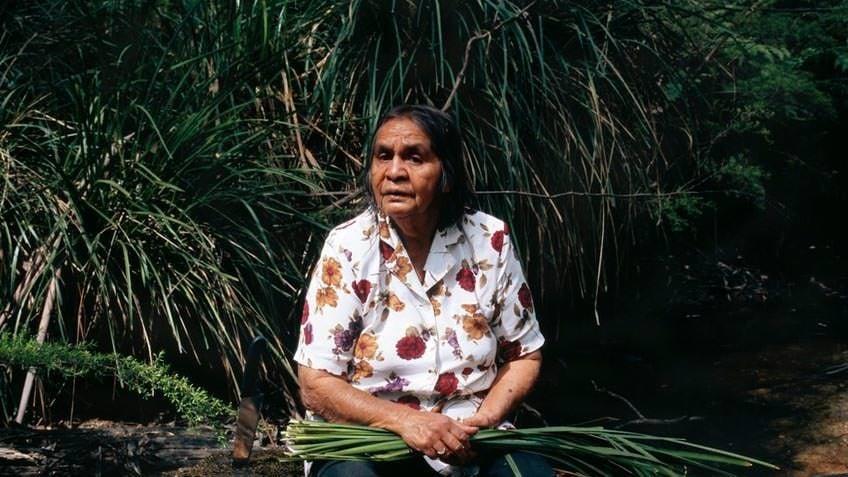Portrait of elder Eadie Terrick weaving a basket; photo by Angela Lynkushka, 20