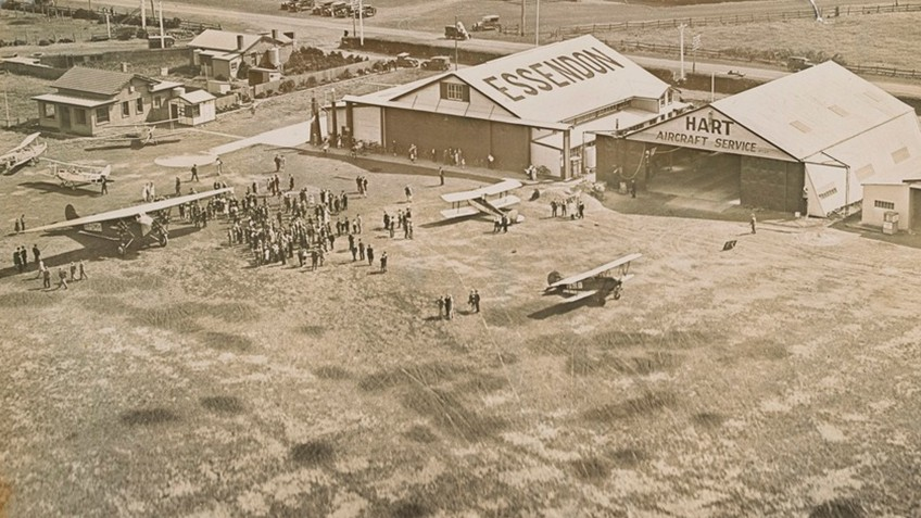 Early 20th-century sepia photo of airport hangars, planes and people