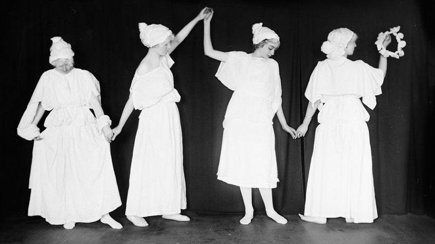B&W photo of four girls in classic Grecian costume dancing on a stage