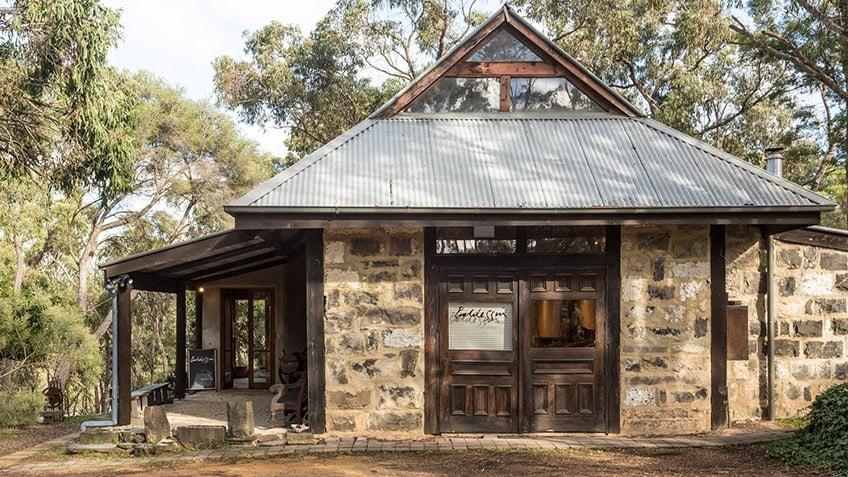bluestone studio with tin roof surrounded by bushland