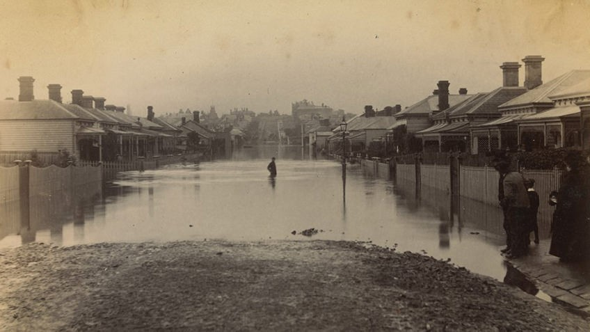 sepia photograph of flood waters in a suburban street, inundating gardens lined with picket fences