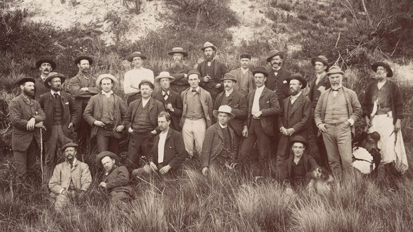 Sepia photo of men in coats and hats, most standing, two reclining, among tussocks, sand dune rising behind them