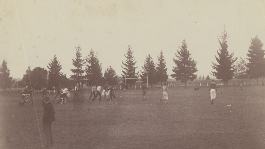Blurry image of men and a dog on a football field with an H-frame goal post in centre back