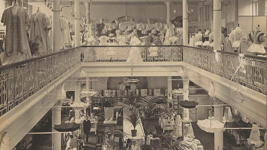 Interior view of elegant shop with ]wrought iron balconies fringing each of the three floors