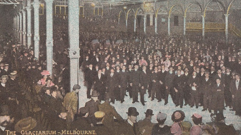 Hand-tinted picture of a large ice-skating rink with arched walls and many people