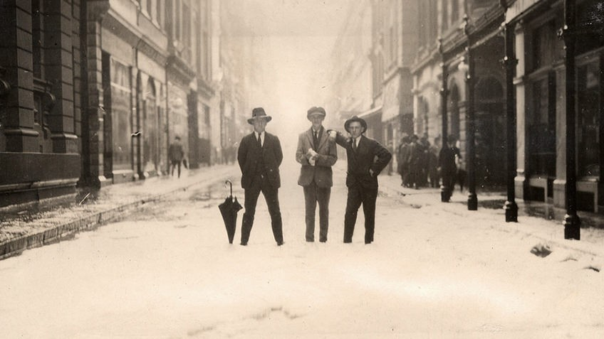 Black and white image of three men standing in a Melbourne street surrounded by hailstones like snow, deep enough to support an umbrella
