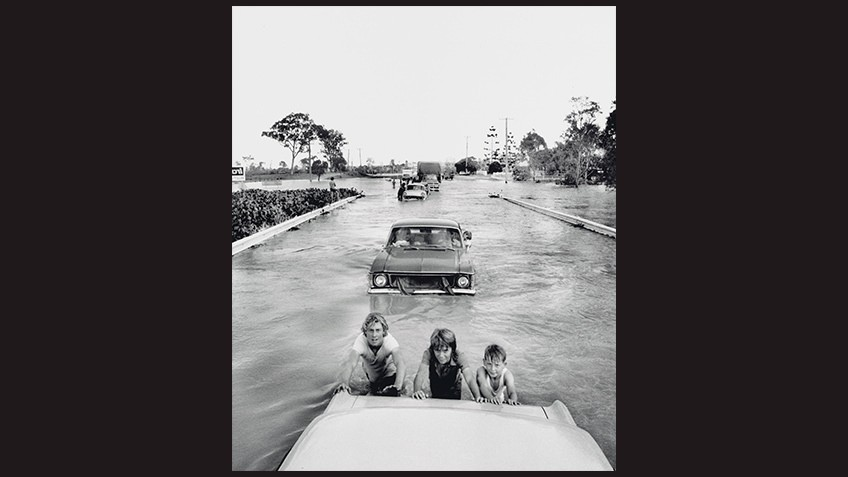 black and white photo of 3 smiling kids pushing a car through floodwaters