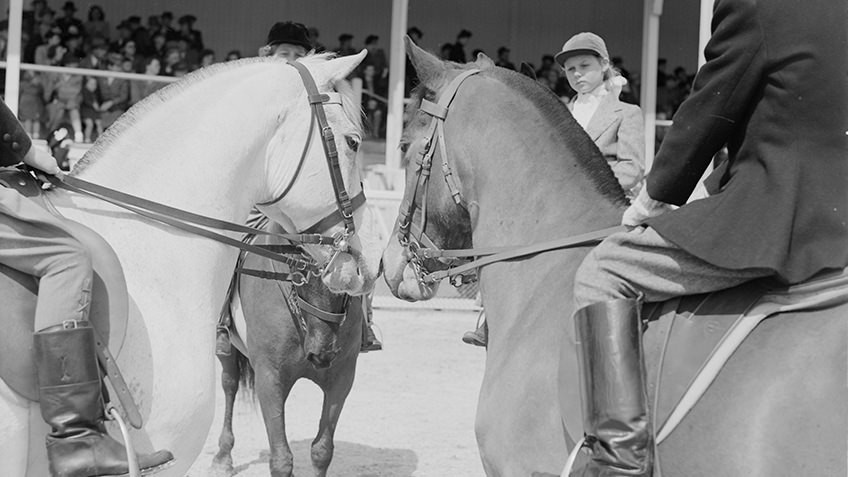 B&W photo of two horses with muzzles touching as a young girl in equestrian helmet looks on