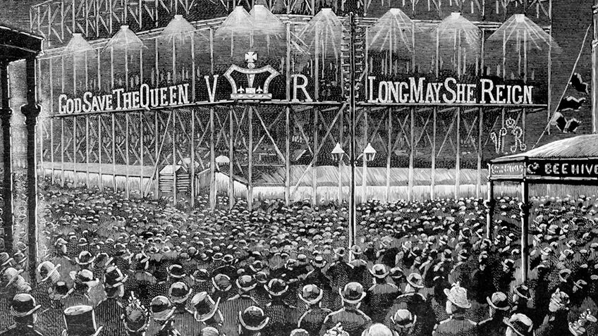 B&W print of hordes of people looking at a grand building lit up with God save the Queen in lights
