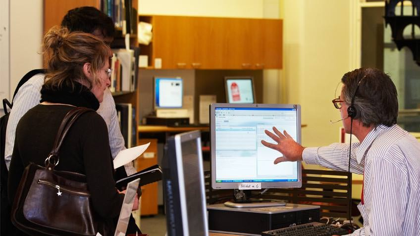 Staff member assisting users at the information desk