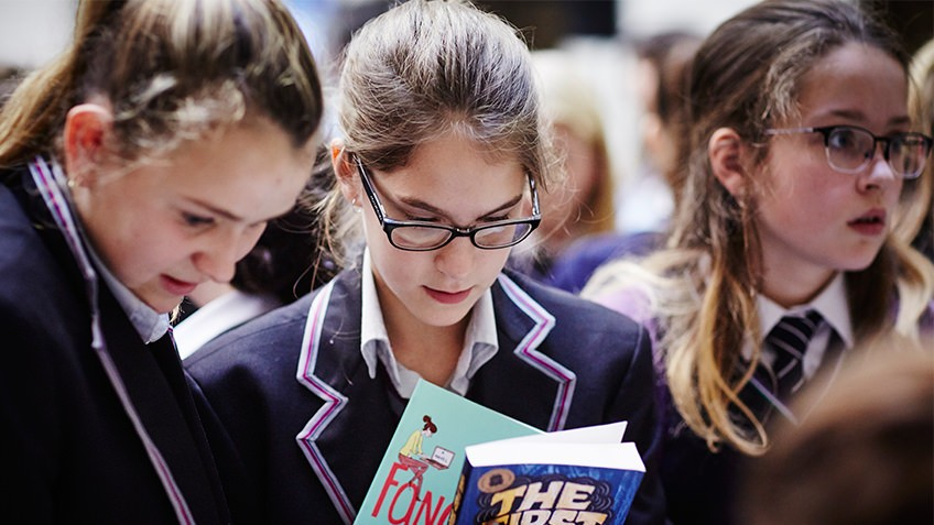 Colour photo of schoolgirls reading Young Adult books