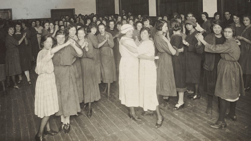 Black and white image of girls and women dancing arm in arm