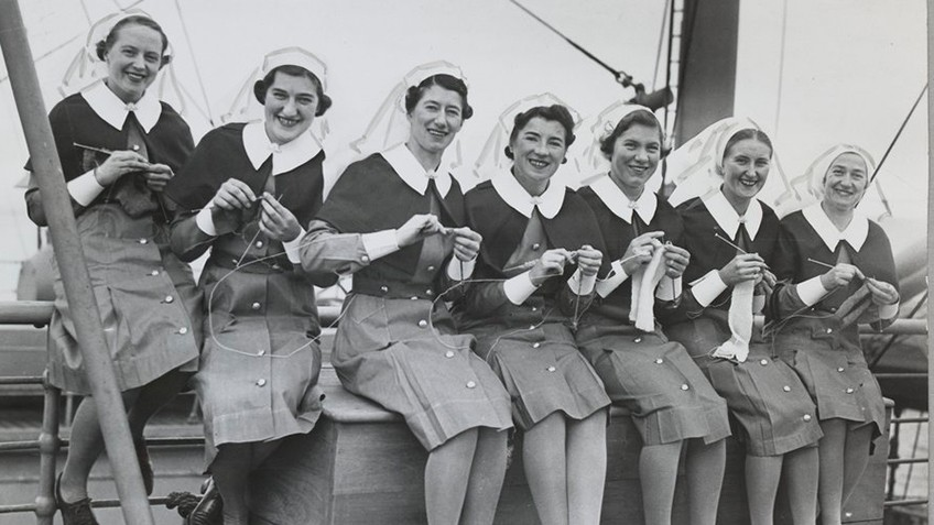 Seven women in WWII nurses uniforms are knitting while perched on the edge of a ship
