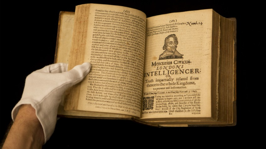 Colour photo of gloved hands holding open a rare copy of the early illustrated news sheet Mercurius Civicus Londons Intelligencer, London, 1643–46