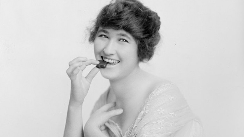 A woman smiles as she places a chocolate in her mouth