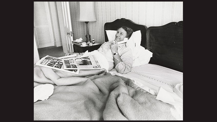 Black and white portrait of smiling Malcolm Fraser in bed speaking on telephone