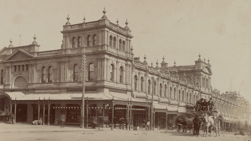 Looking across a wide intersection towards a two-storey Italianate building with arched windows