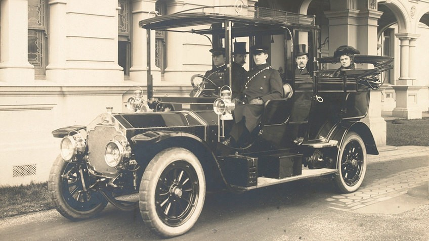 Early-20th-century photo of early motor vehicle with well-to-do passengers and chauffeurs under the porte-cochere of a mansion