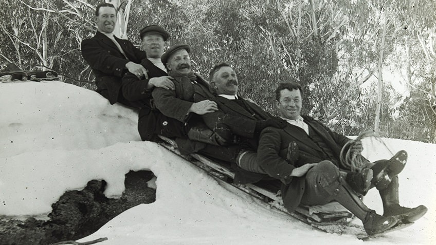 Black and white photo of five men on a toboggan about to descend a snowy hill