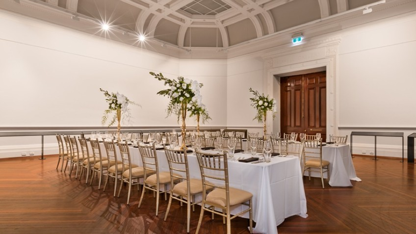Long tables are laid with white cloths, crystal glasses and flowers in an ornate heritage room