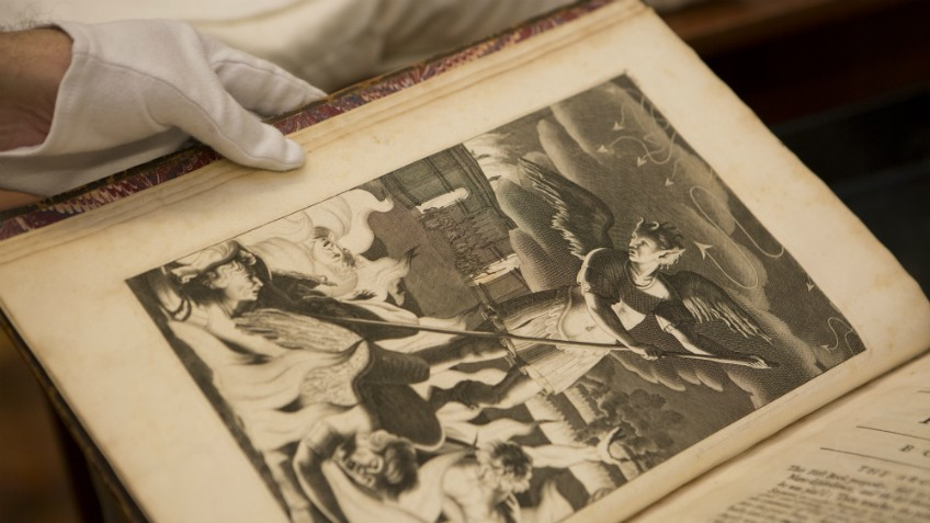 Colour photo of gloved hands holding rare edition of John Milton, Paradise lost, London, 1688 (first illustrated edition)