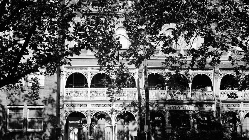 B&W photo of three-storey terraces with wrought iron verandahs, balustrade at roofline, upper windows flanked by pilasters, stone wall with iron railing fence in front.
