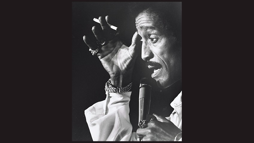 black and white portrait of Sammy Davis Jnr with microphone and cigarette