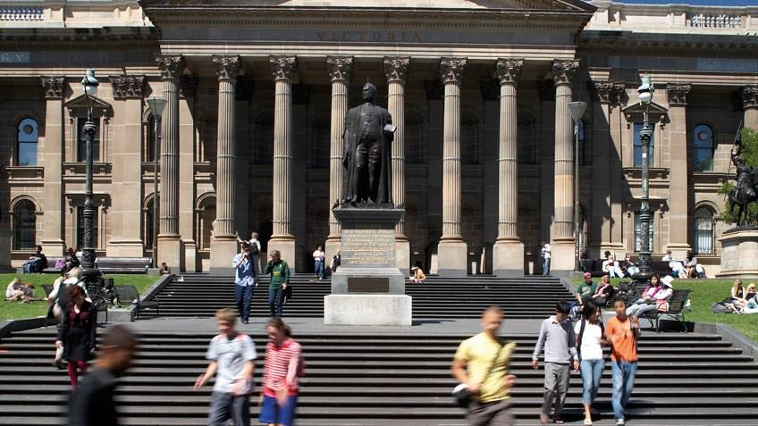 Colour photo of State Library Victoria front steps and portico, with statue of Redmond Barry and people walking down the steps
