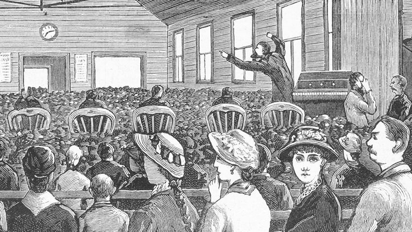Photo of a preacher giving a sermon to a room full of people