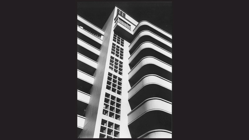 black background with striking close-up of modernist multistorey block of flats
