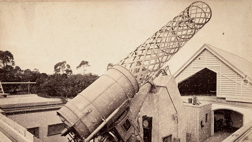 A giant telescope is aimed skywards above a nearby roof and trees