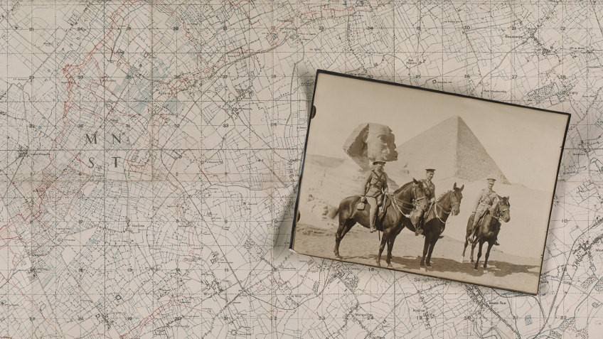 Three uniformed men pose on horses before the Sphinx and an Egyptian pyramid