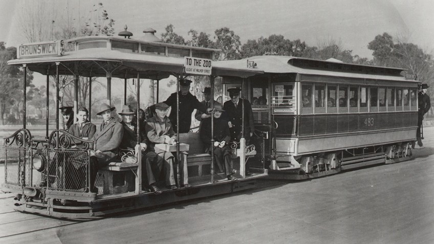 Open sided cable tram with passengers and conductor and a closed carriage attached